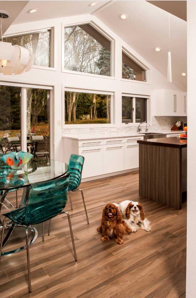 A mesa dessa cozinha moderna ficou perfeita com as cadeiras de acrílico na cor azul e pés metálicos