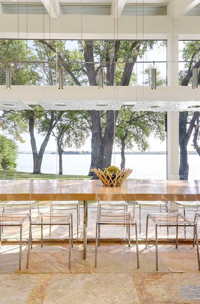 Sala de jantar moderna com jogo de cadeiras de acrílico transparente; perceba quanta leveza e fluidez que as cadeiras de acrílico trazem para o ambiente