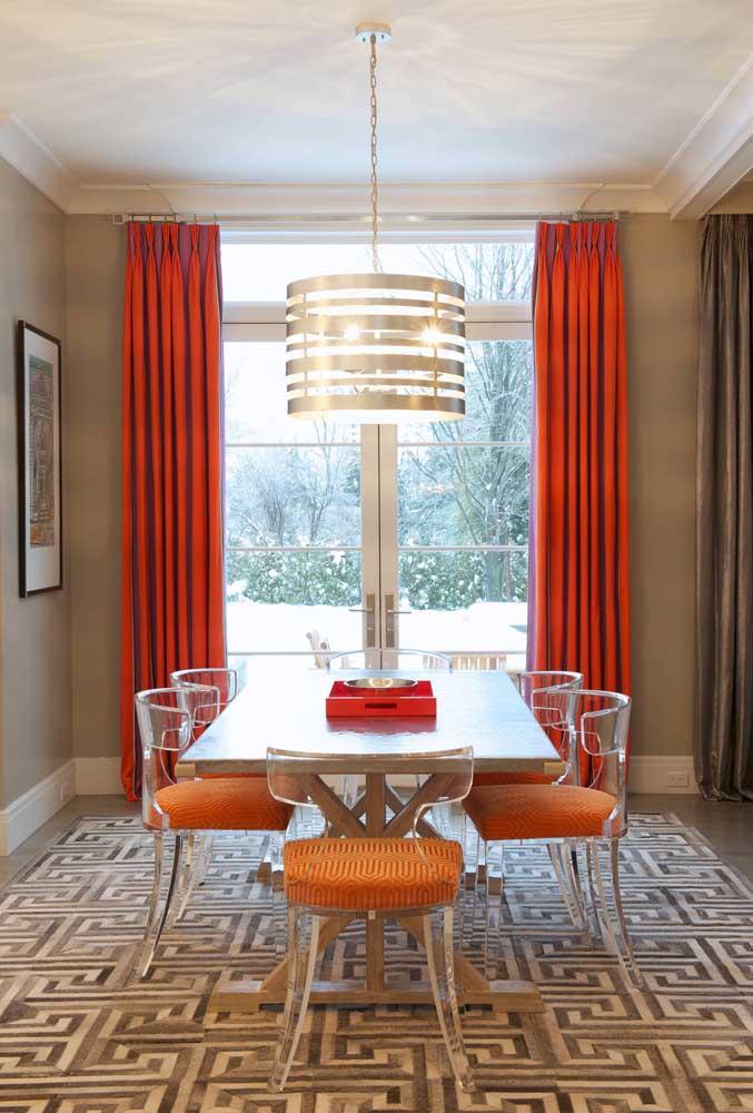 Os tons quentes da sala de jantar foram amenizados pelas cadeiras em acrílico transparente