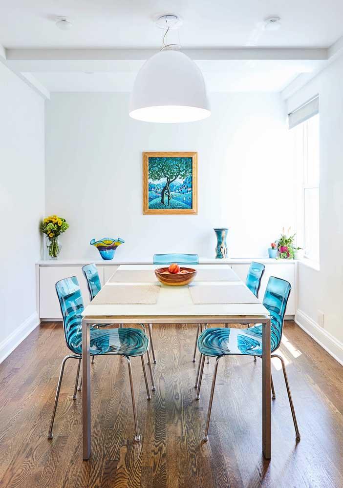 Essa sala de jantar clean trouxe cadeiras de acrílico azul para combinar com os detalhes da decor