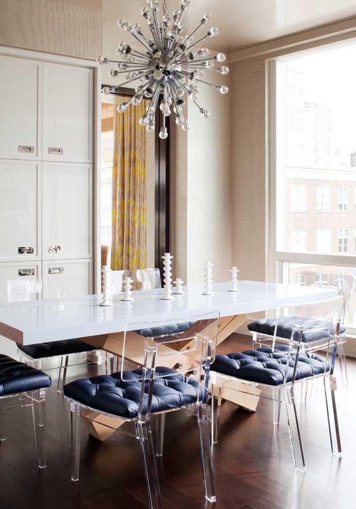 Sala de jantar com cadeiras de acrílico; destaque para o assento estofado com acabamento capitonê
