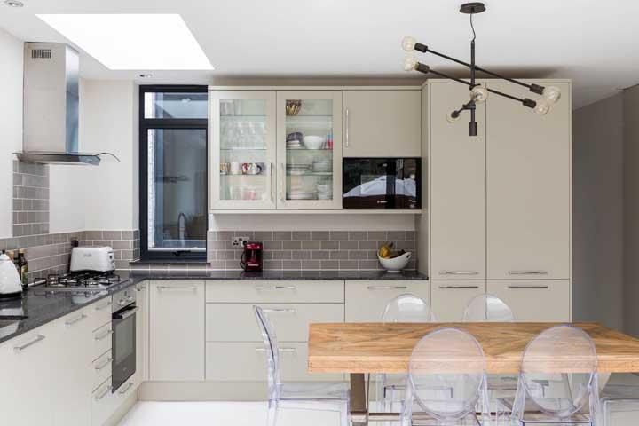 Cozinha moderna com cadeiras de acrílico transparente; repare que as peças ajudam a manter a neutralidade do ambiente