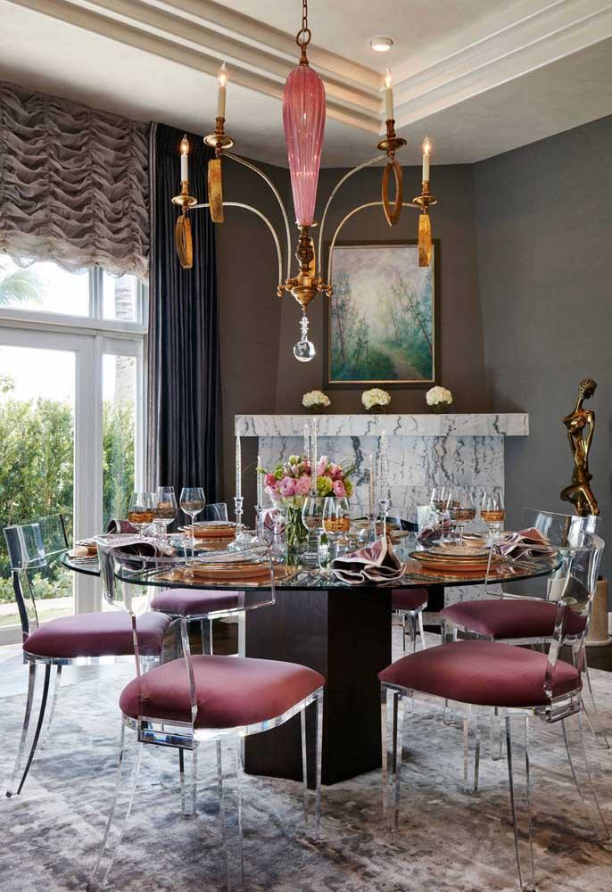 A sala de jantar clássica combinou perfeitamente com as cadeiras em acrílico, que por sua vez, combinam com a mesa redonda com tampo de vidro