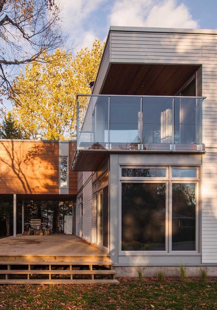 Casa em L com varanda simples, acabamento em madeira e grandes janelas com vista para a varanda
