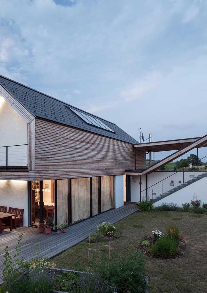 Casa em L simples com varanda e fachada em madeira; destaque para o terraço ao fundo da casa