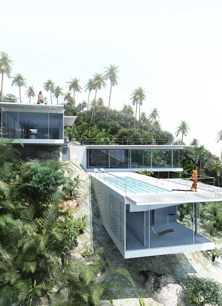 Casa em L com terraço e paredes de vidro para favorecer a vista deslumbrante