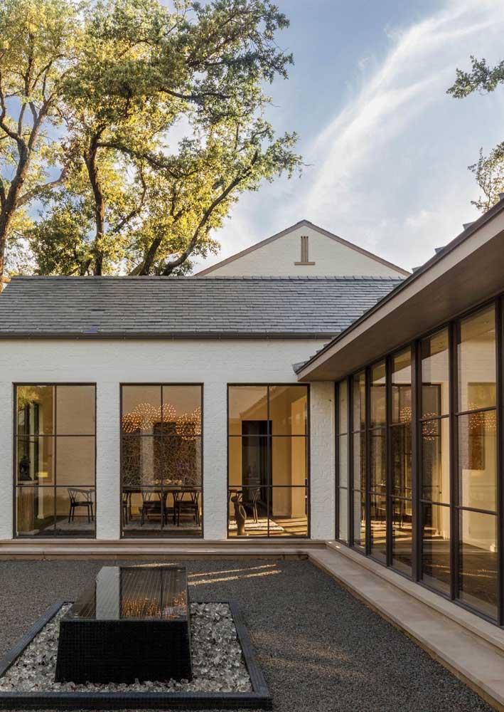 Casa em L simples com grandes janelas para o jardim
