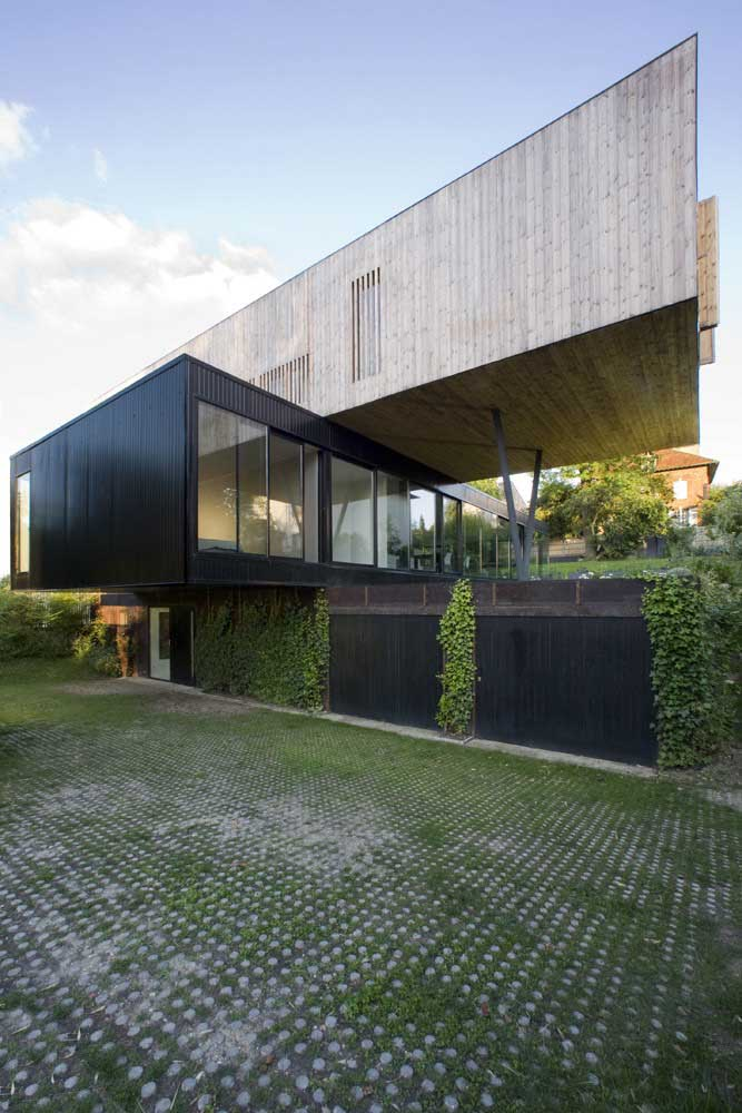 Casa moderna em L com grandes janelas; destaque para o conceito contemporâneo da obra