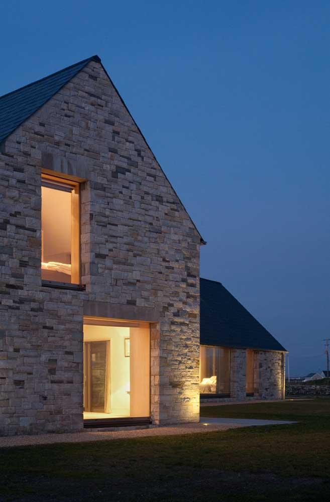 Fundos de uma casa em L simples, com dois andares e vista para o jardim