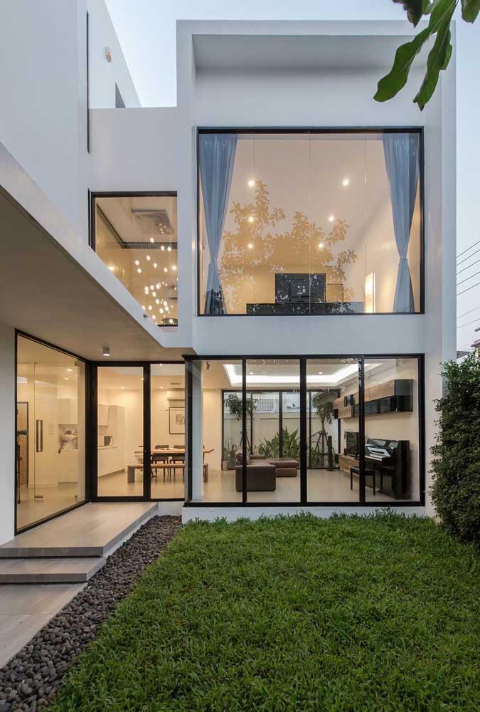 Essa casa em L simples contou com portas de vidro e janelas grandes com vista para o jardim
