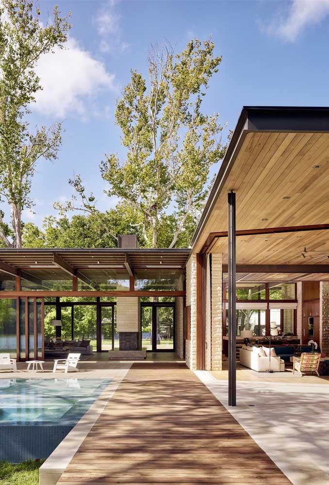 Aqui, a casa em L contorna a piscina construída no centro do quintal