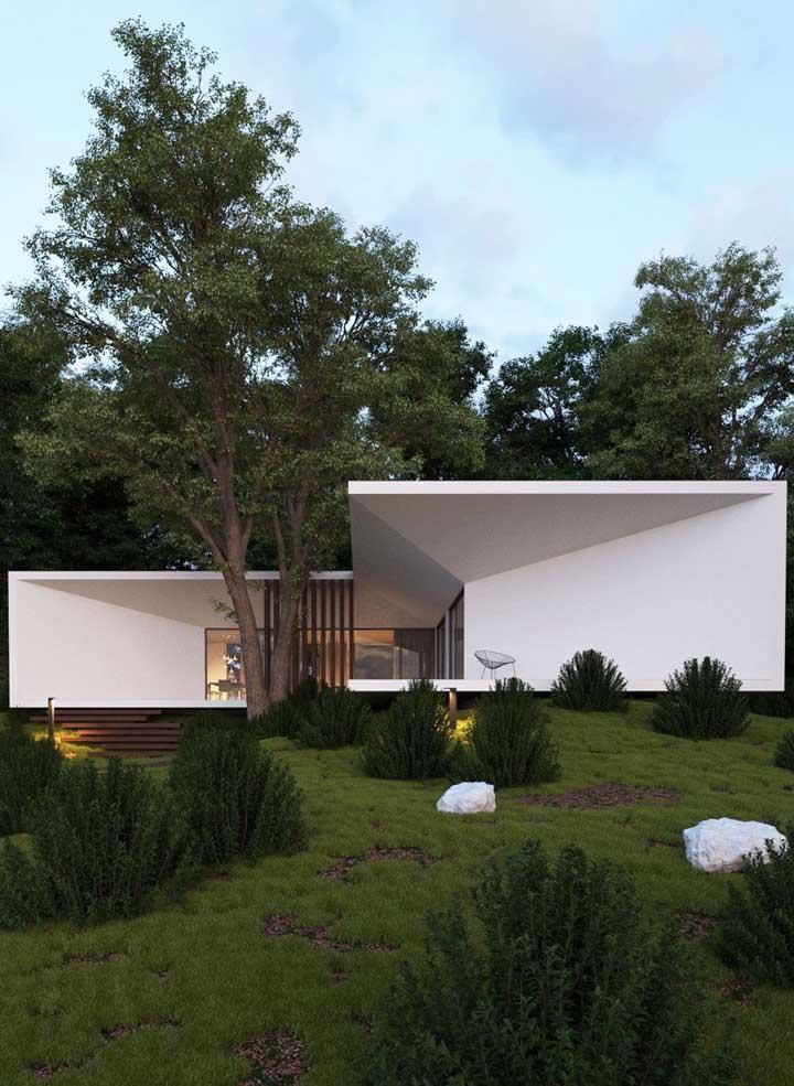 Casa em L com parede de vidro e vista para o jardim
