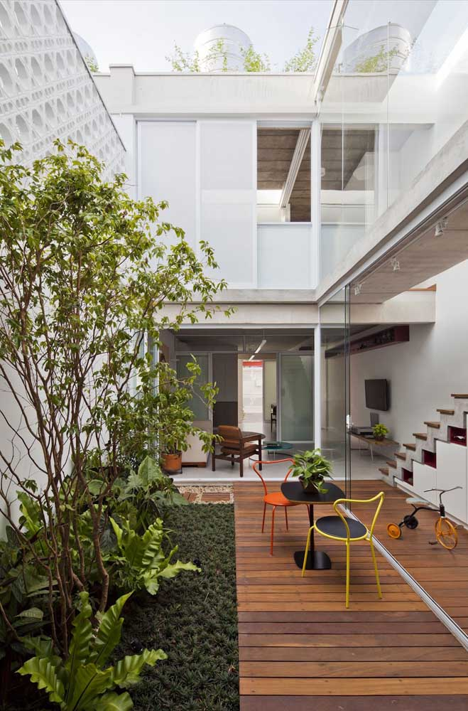 Casa em L em formato sobrado com cômodos integrados e extensas janelas de vidro