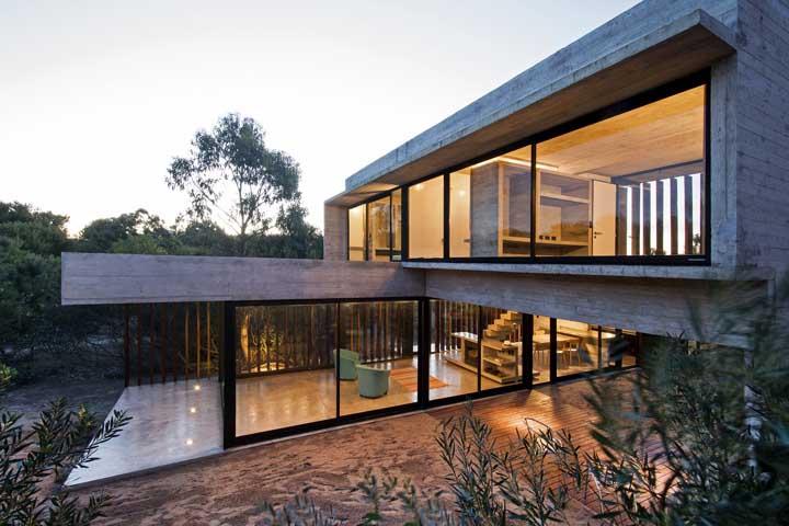 Casa com janelas grandes e planta em L; destaque para a iluminação que faz toda diferença no projeto