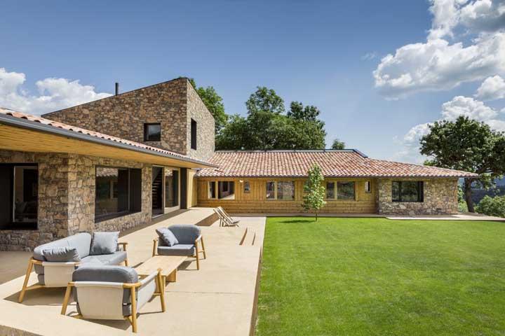 Casa em L com uma varanda simples e um jardim perfeito