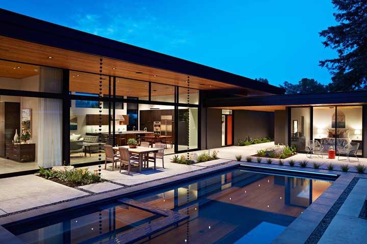 Casa luxuosa em L, com pé direito duplo e vista para a piscina
