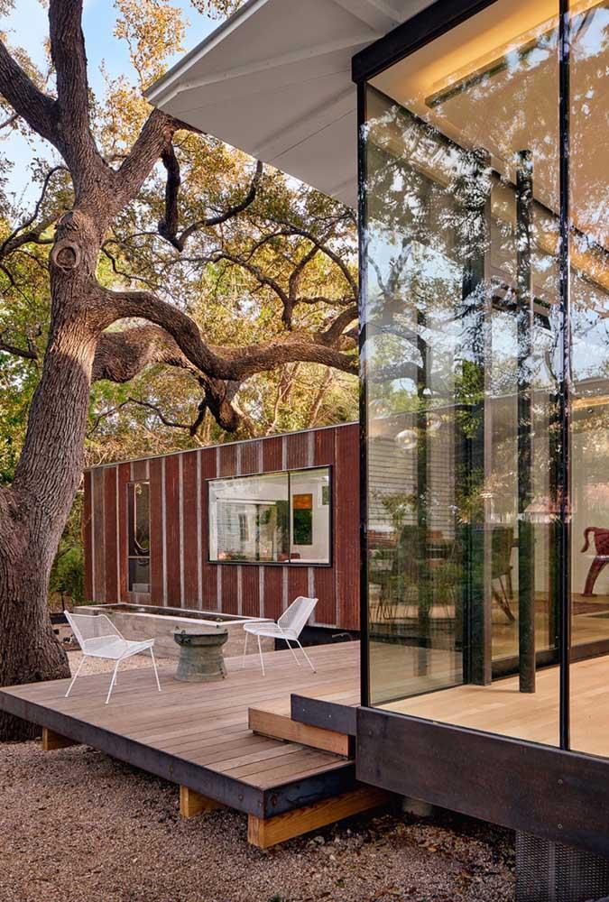 Modelo de casa em L rústica com paredes de vidro e varanda para o jardim da residência