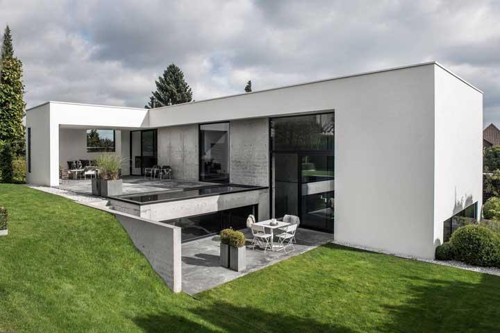 Casa moderna em L; destaque para os tons neutros da fachada