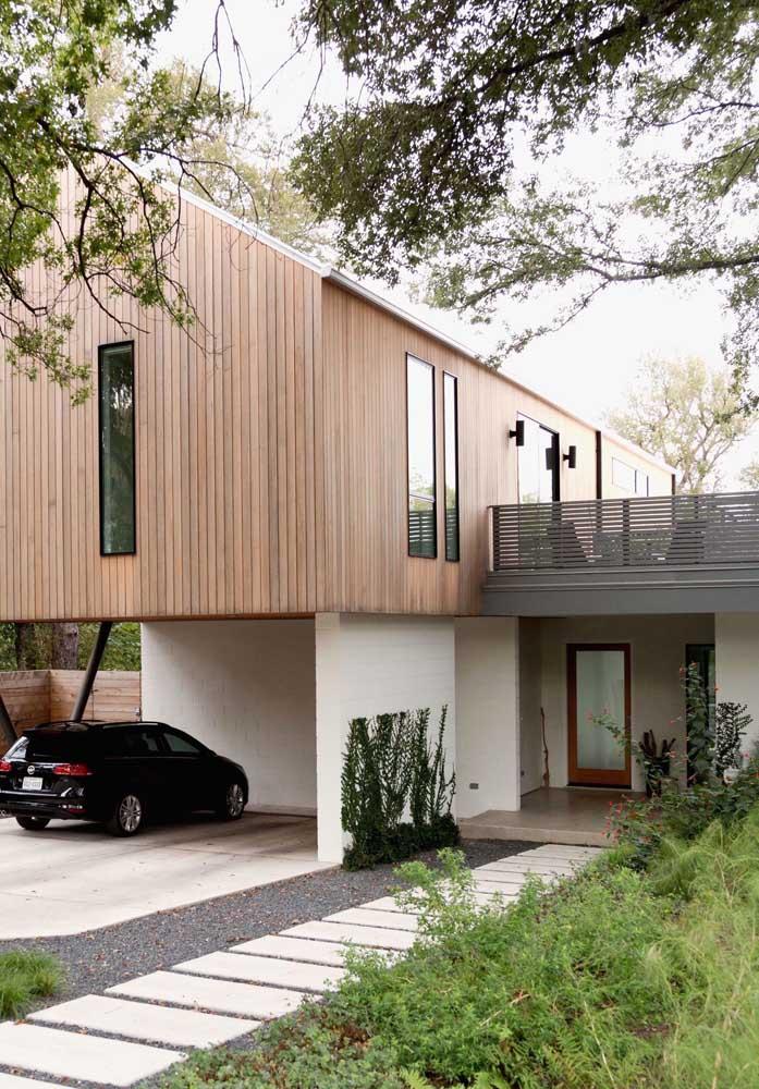 Casa em L com varanda e garagem interna; destaque para a fachada de madeira