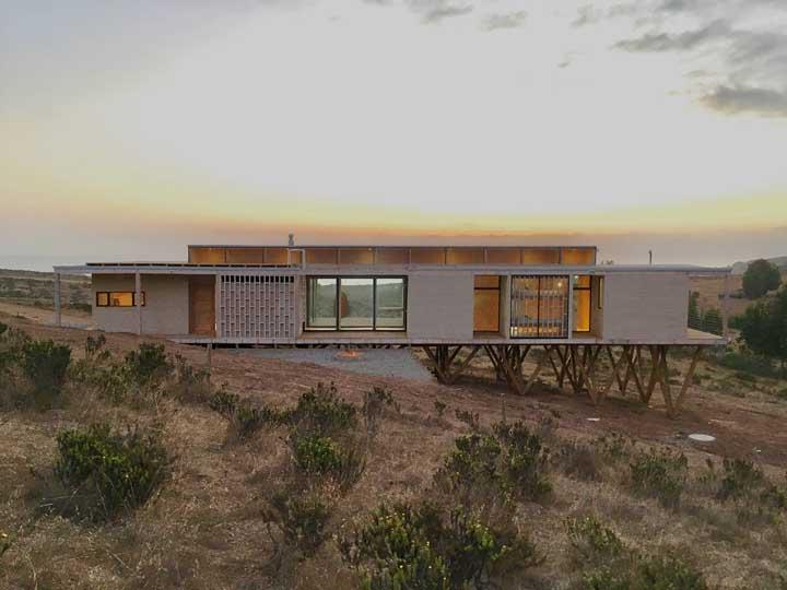 Mais uma inspiração de casa planejada para terrenos maiores; o imóvel foi construído em formato térreo, mas deixou à vista a estrutura de sustentação e nivelação