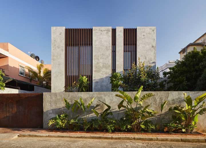 Casa planejada em estilo moderno com fachada de cimento queimado e muro cercado por plantas