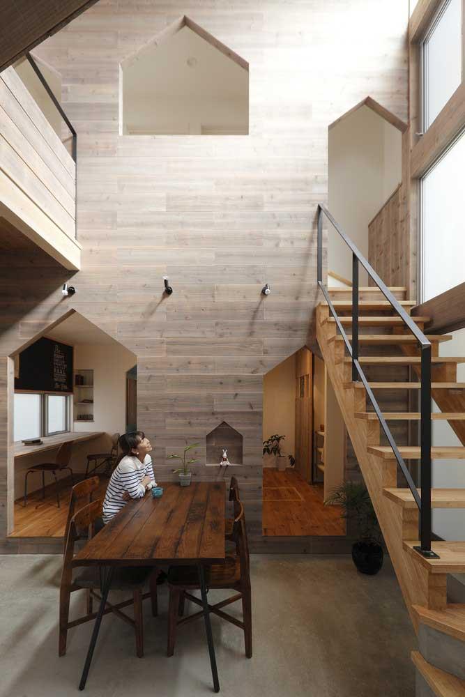 Casa planejada com pé direito duplo; destaque para a parte interna revestida em madeira