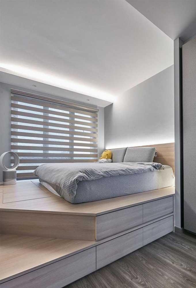 Quarto planejado com cama no chão sobre um pequeno mezanino; destaque para o suporte com gavetas construído abaixo do móvel