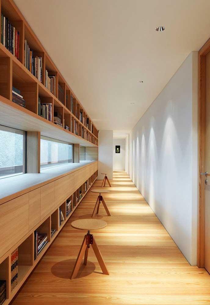 O corredor dessa casa planejada ganhou a companhia de prateleiras para compor a pequena biblioteca particular