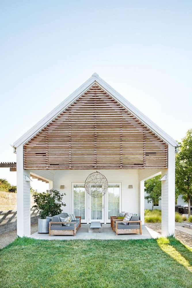 A casa simples foi planejada com uma linda varanda coberta e fachada com detalhes em madeira
