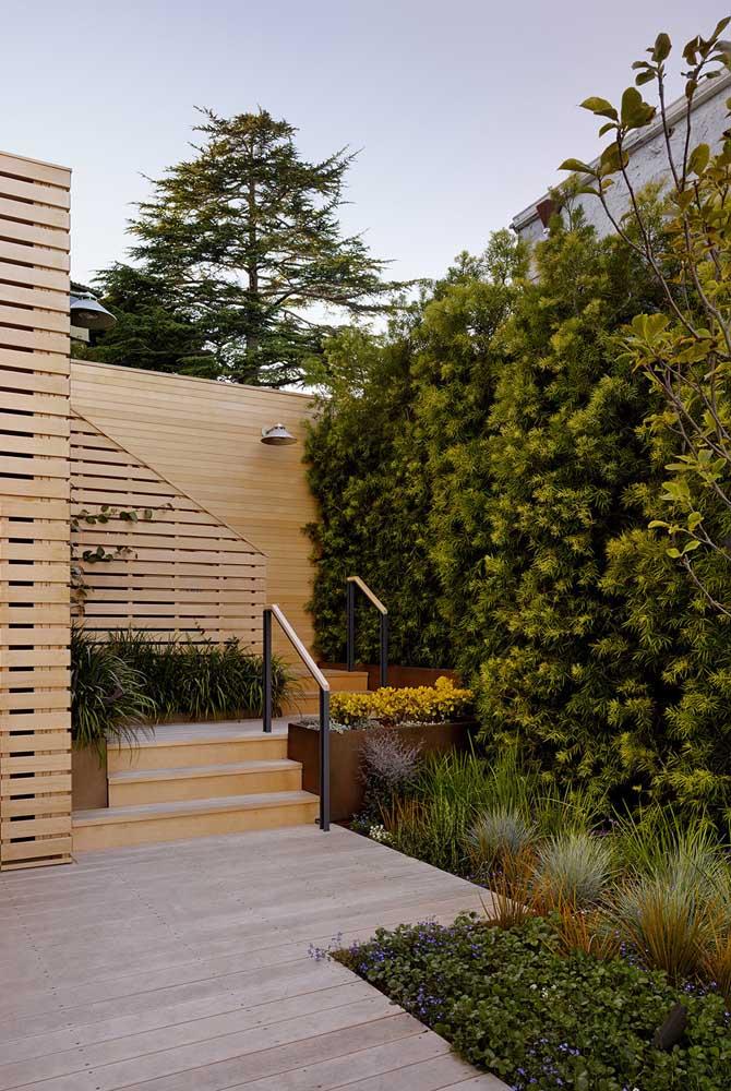 A entrada em madeira combinou super bem com a cerca viva em folhas amarelo-esverdeadas