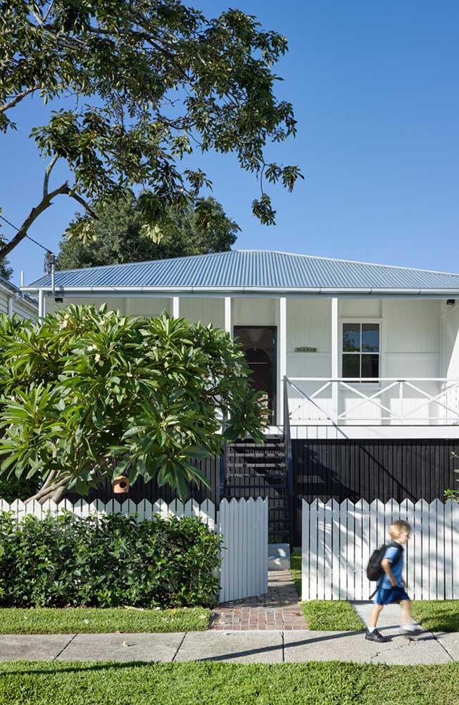 Para não esconder a linda cerca de madeira da casa, a opção foi por uma cerca viva de pequeno porte