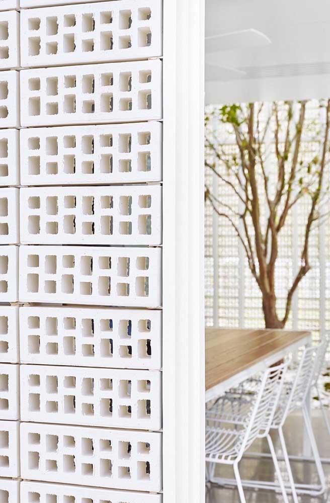 Parede de cobogós delimitando a sala de jantar de outros ambientes; repare que os cobogós simples de cerâmica crua receberam pintura para seguir a estética do espaço