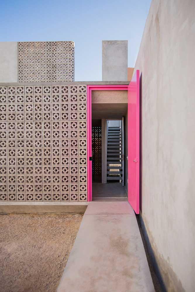 Os cobogós simples de cerâmica ganharam uma companhia de arrasar: a porta rosa pink