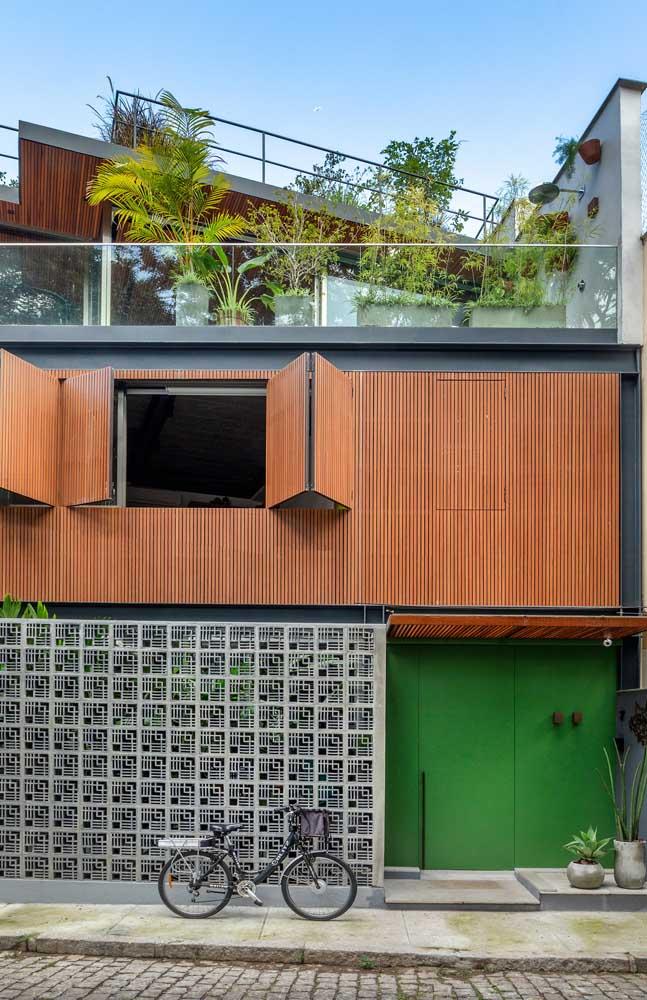 Essa fachada graciosa conta com um muro de cobogós em companhia do painel de madeira