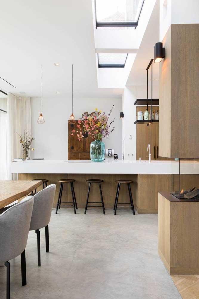 Cozinha gourmet integrada à sala de jantar, delimitadas visualmente pelo balcão, semelhante ao que acontece com a cozinha americana