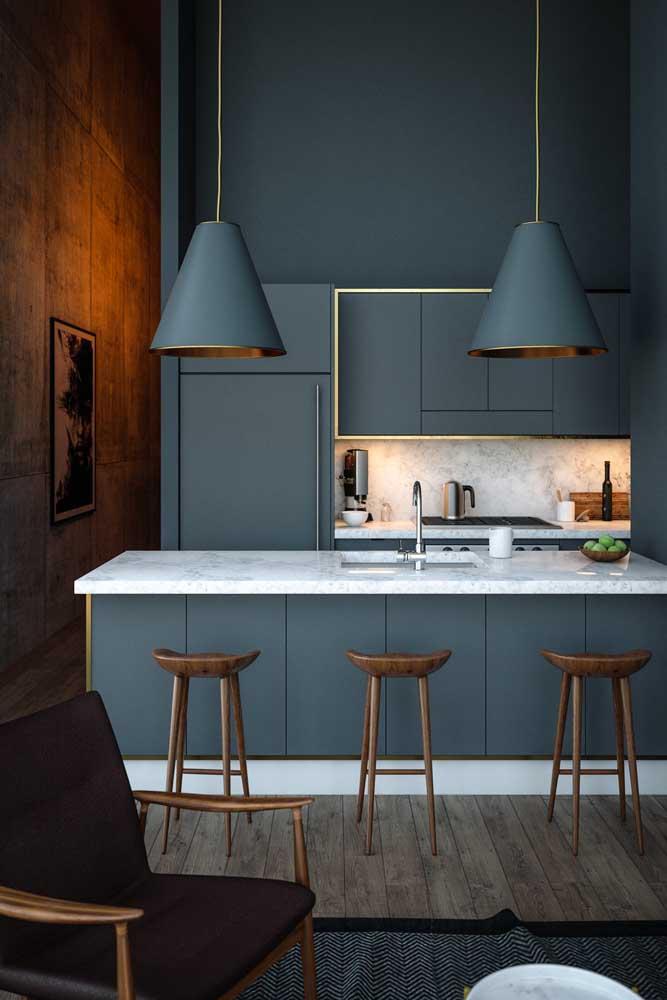 Moderna e sofisticada, essa cozinha gourmet assumiu tons de azul na parede, nos armários e luminárias; o cimento queimado e o mármore completam a proposta