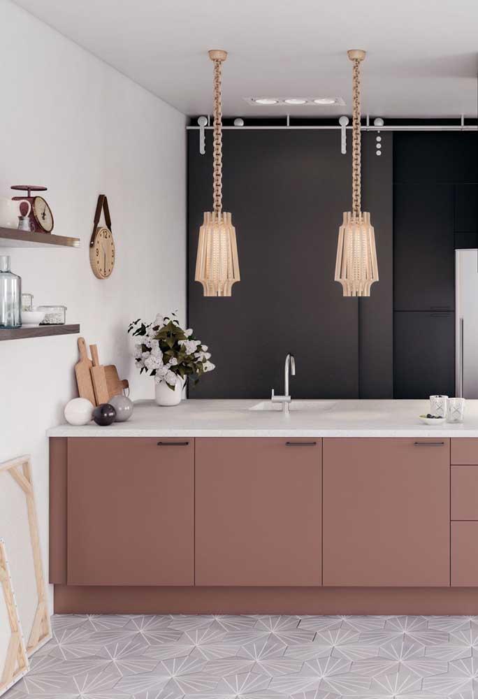 Cozinha gourmet com bancada central; o tom de rosa queimado dos armários em conjunto com o mármore e as luminárias douradas garantiu o toque de elegância e refinamento ao projeto