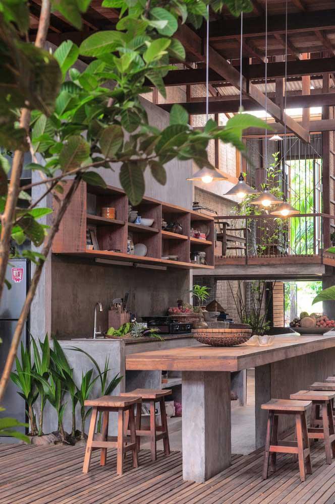 Inspiração apaixonante de cozinha gourmet rústica em área externa; o uso da madeira e das plantas são fundamentais para garantir o estilo acolhedor do espaço