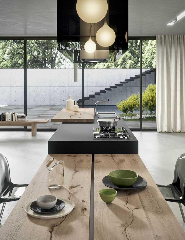 Nessa cozinha gourmet, a grande abertura em vidro integra os ambientes interno e externo