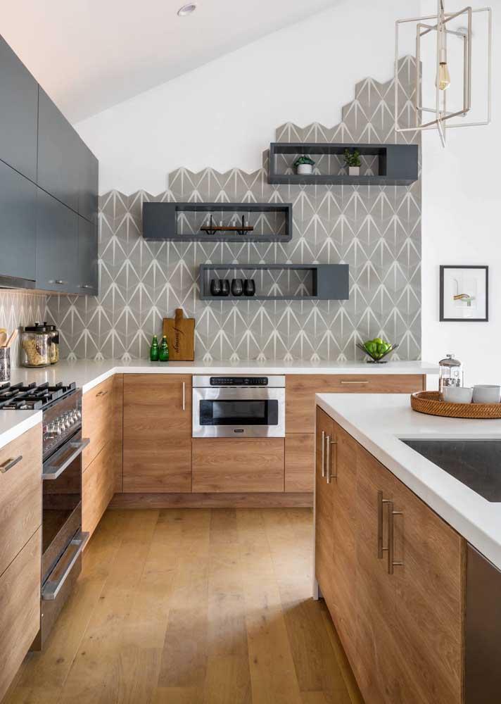 Já aqui, o mix entre o tom amadeirado e a cor cinza cria um estilo moderno e levemente rústico para a cozinha gourmet