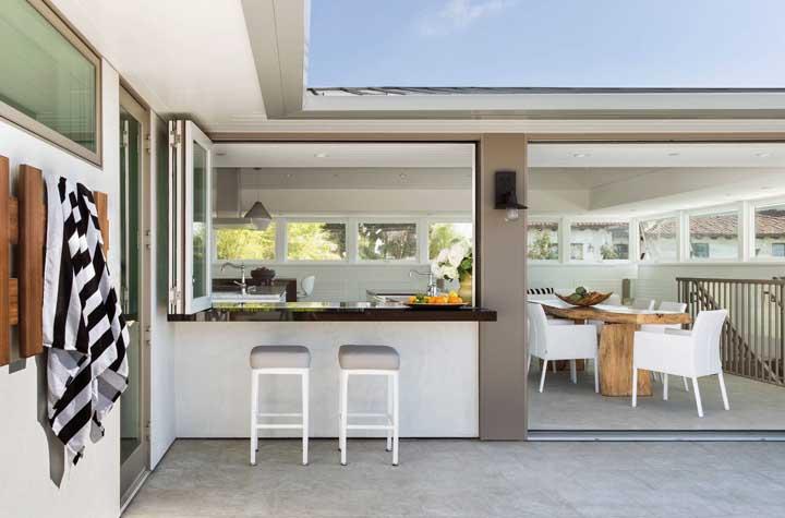 Aqui, o balcão faz a ligação entre a área interna – cozinha gourmet - e externa – varanda