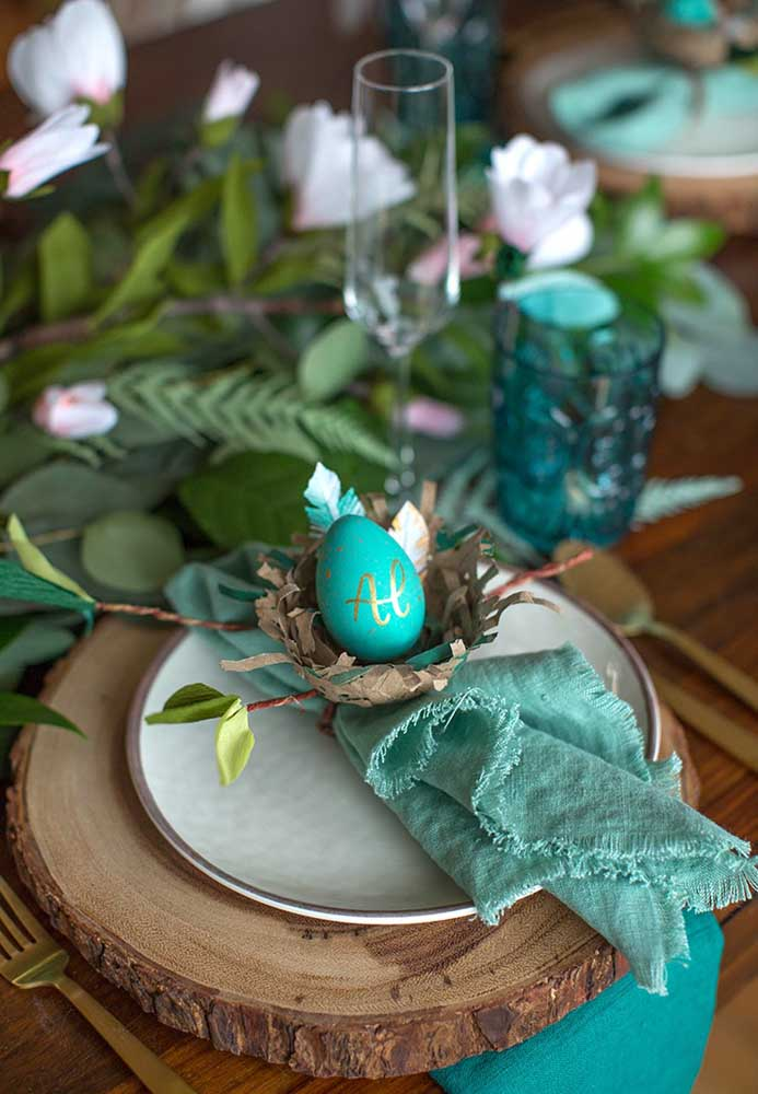 Quer apostar em uma decoração mais rústica para a Páscoa? Use um pedaço de madeira como jogo americano e decore o prato com um ovo pintado dentro de um cesto.
