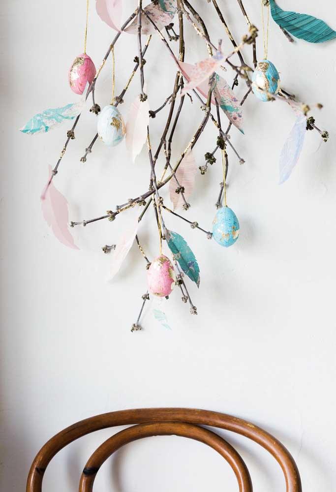 Reaproveite alguns galhos de árvores para fazer uma decoração com ovos personalizados.