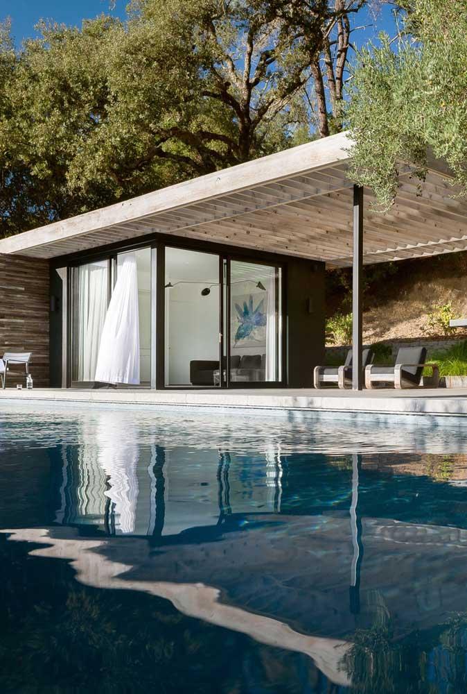 A casa da piscina ficou perfeita na edícula com portas de vidro de correr e varanda aberta