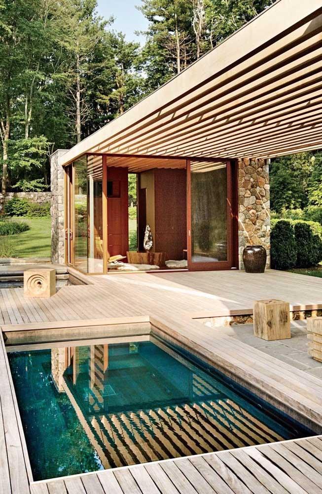 Aqui, o que chama a atenção é a combinação de pedras e madeira na fachada da edícula