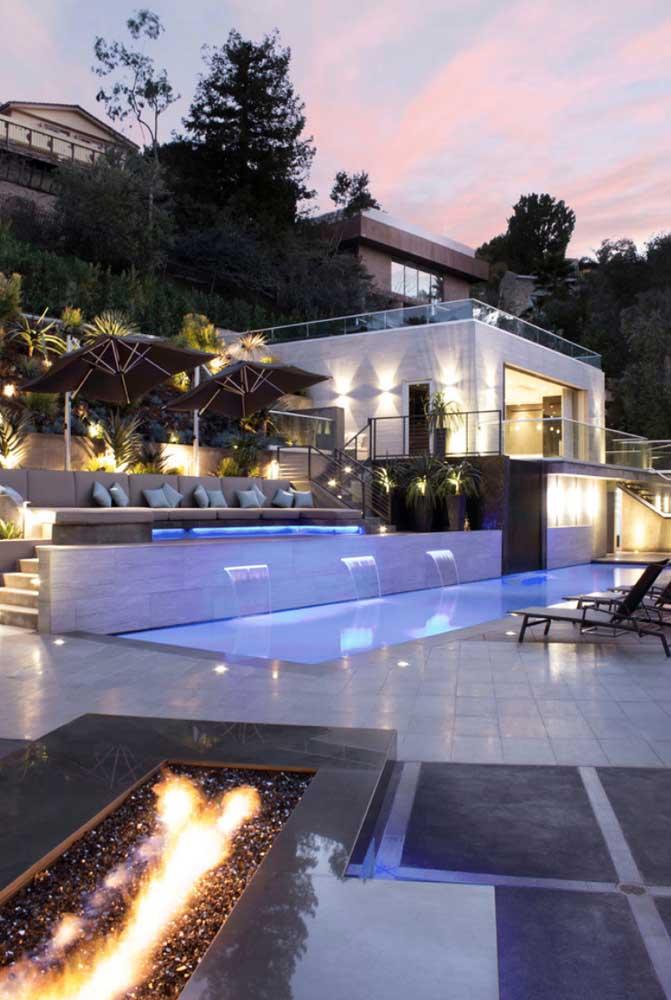 Edícula com escada para acesso à piscina; a iluminação completa o visual externo do espaço