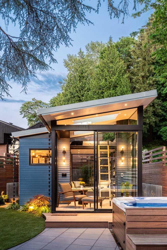 Edícula moderna com estrutura em madeira construída nos fundos do jardim da casa principal