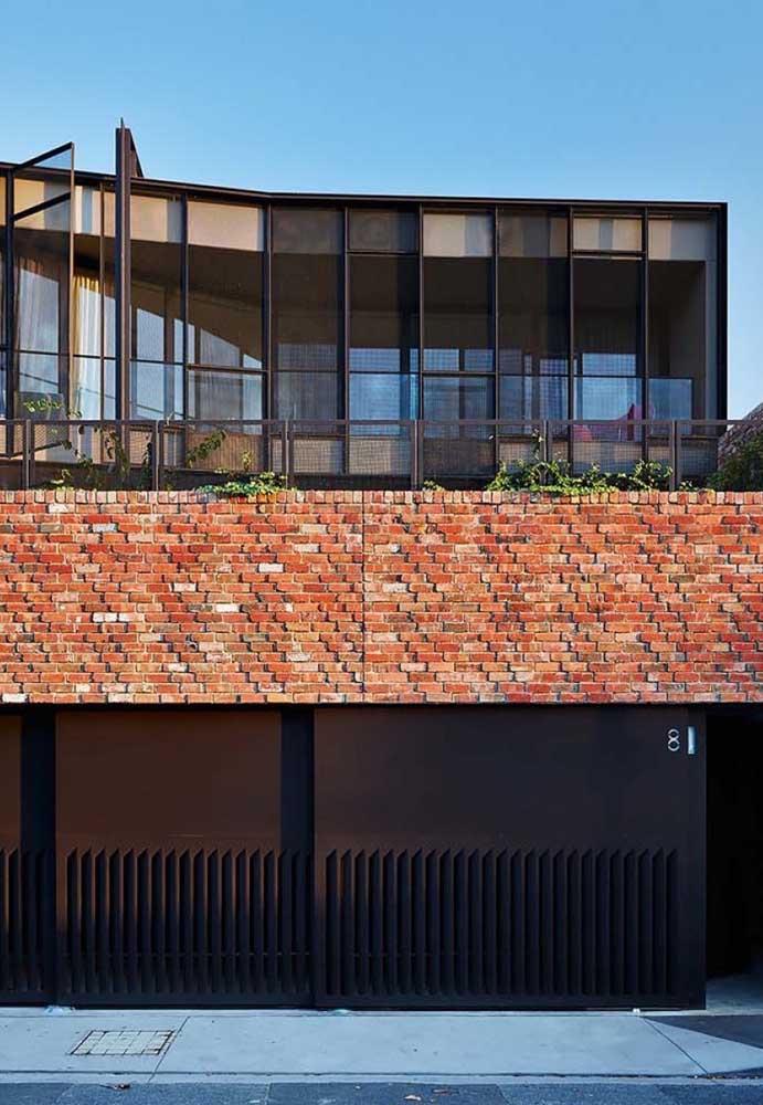 Fachada de muro com tijolo à vista e portão de ferro; uma opção rústica e industrial