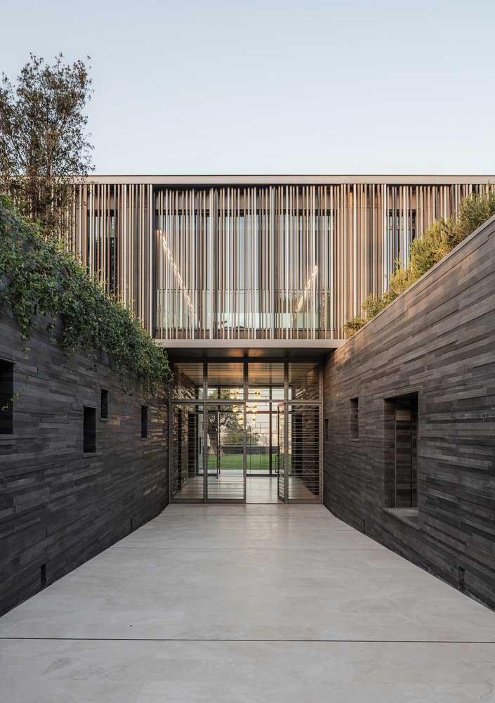 Entrada de uma casa moderna com fachada de muro em filetes de pedras escuras