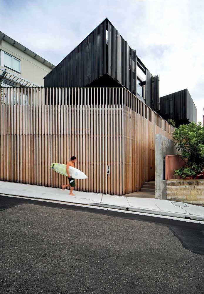 Fachada de muro criativa feita com ripas de madeira; o visual visto do lado de fora é incrível